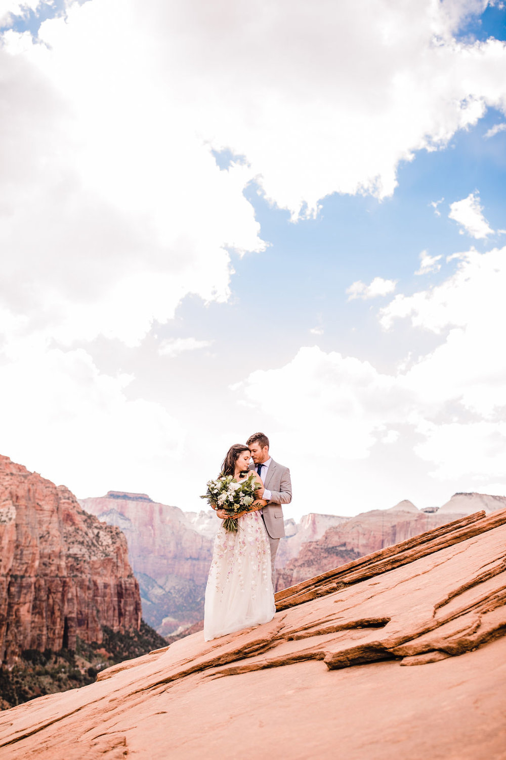 best page arizona formal photographer hugging romantic white clouds bohemian bride red rocks
