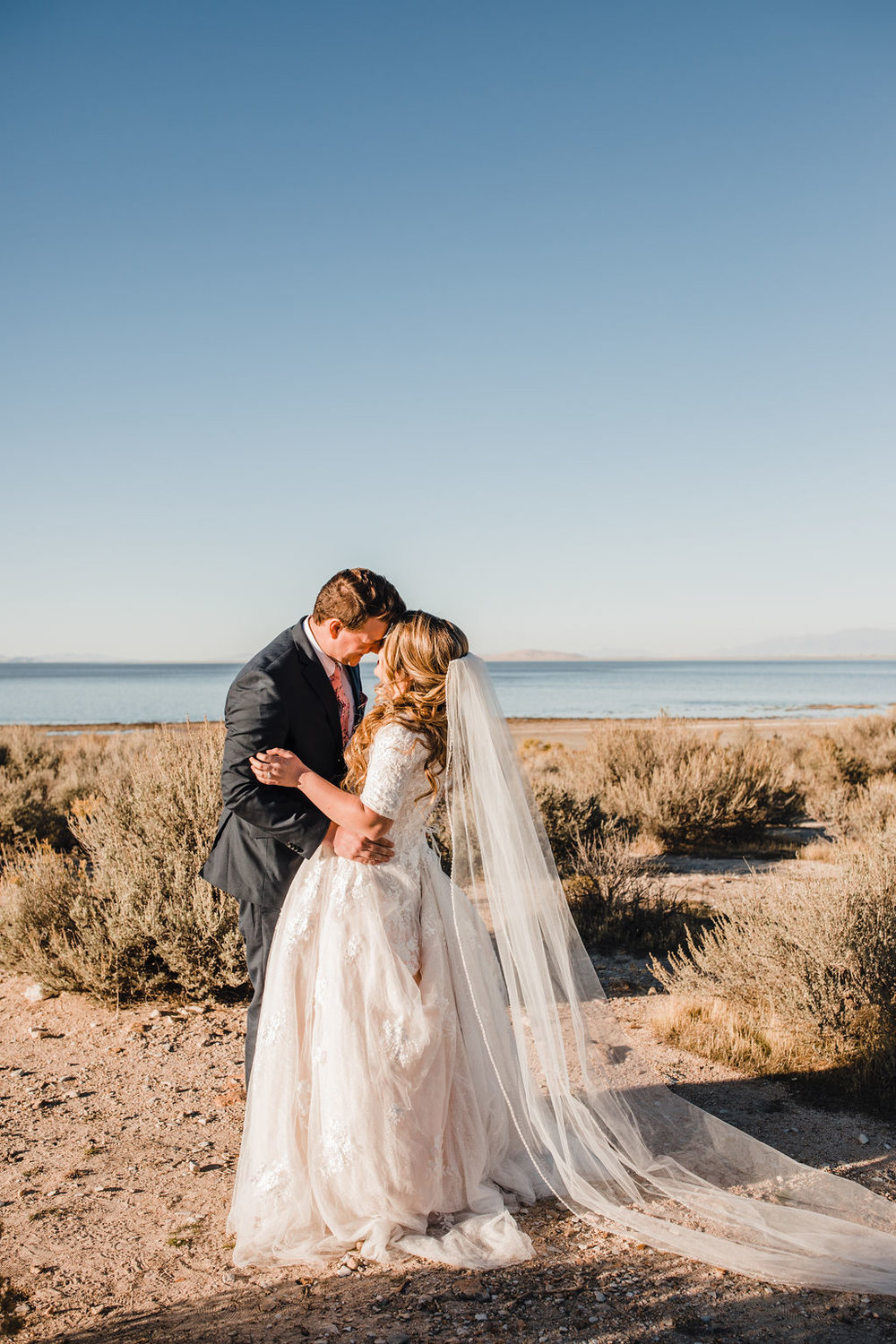 professional salt lake city wedding photographer long veil sand antelope island clear skies kissing romantic