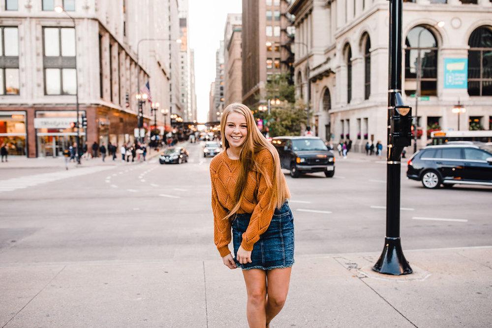 city scape sky scraper senior portrait photographer denim skirt busy street playful smile