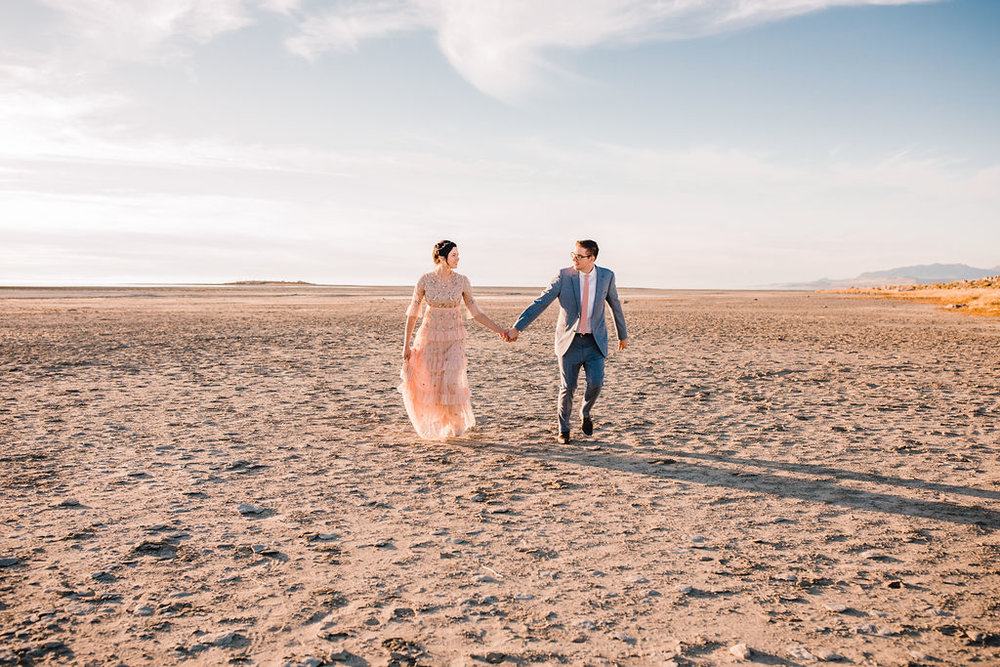 bride and groom running across the sand during sunset at antelope island pink wedding dress gown with jewels vintage bohemian wedding style salt lake city utah