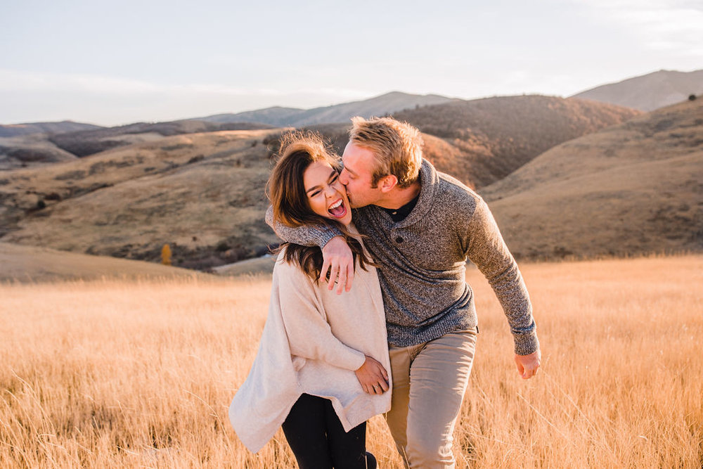 couple hugging laughing kissing fields mountaintop adventurous classy engagement photos logan utah