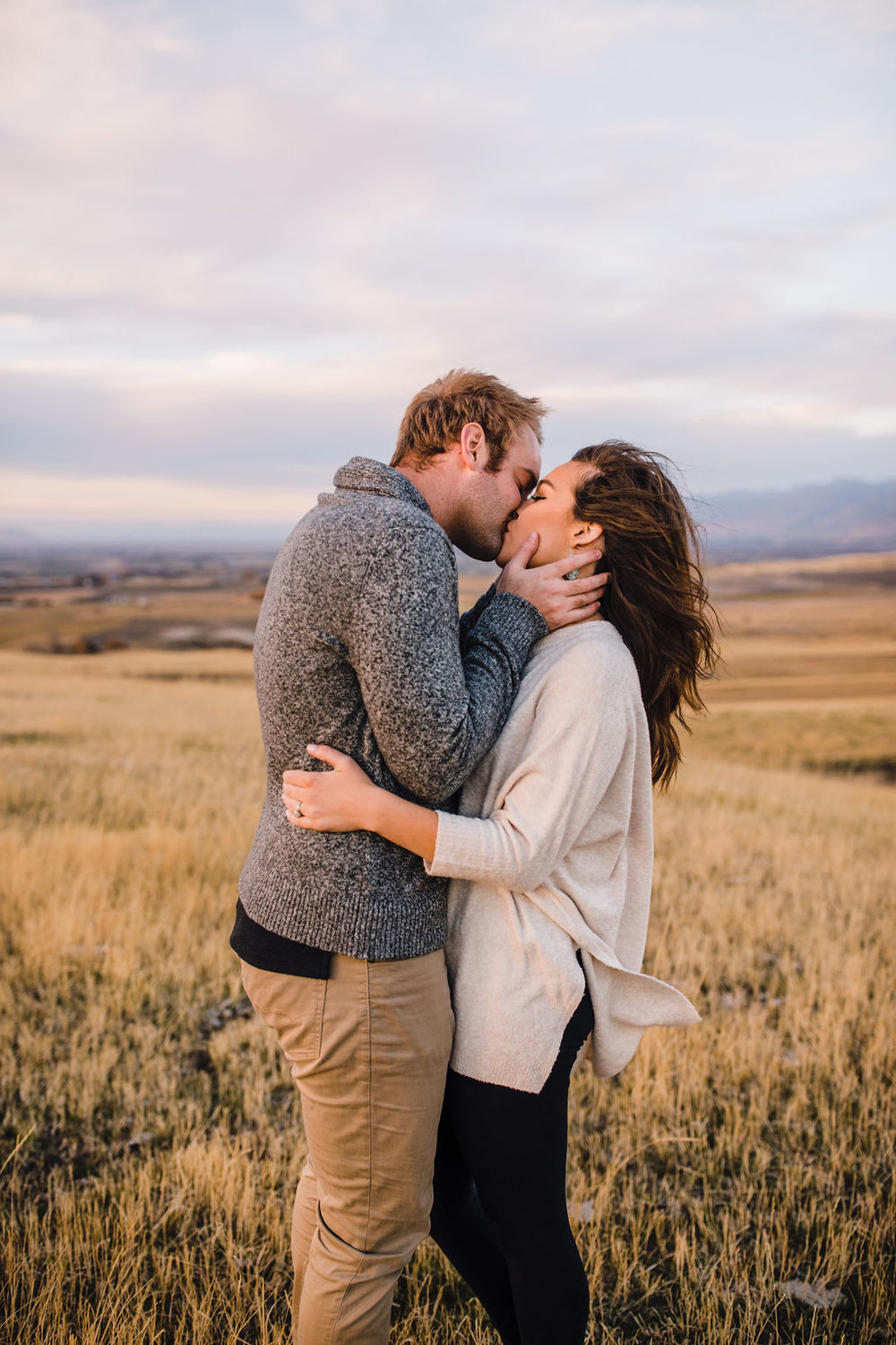 windy engagement photos couple kissing romantic hugging northern utah wedding photographer