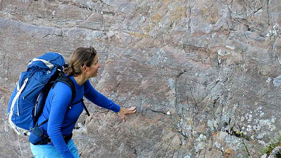 Turen forbi Knekkevasshytta går i sneglefart. Stadig vekk må geolog Denise Rüther lene seg inn til fjellveggen og studere «årringane» i berget.