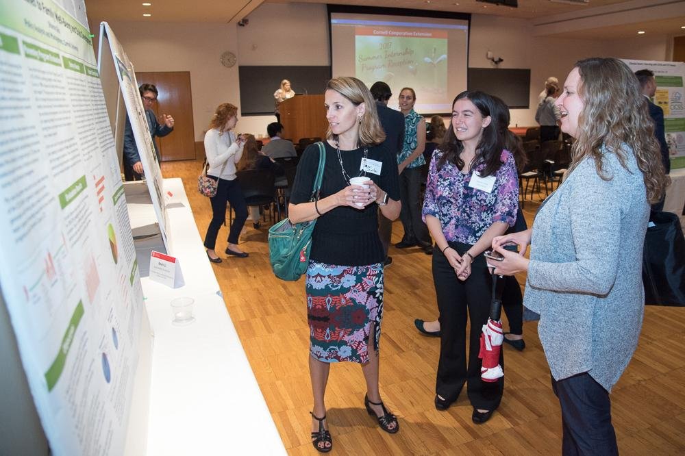 Project 2Gen student Sharon Glick (center) presenting her research at a Cornell Cooperative Extension event. She talks with Project 2Gen co-directors Rachel Dunifon (left) and Laura Tach (right)