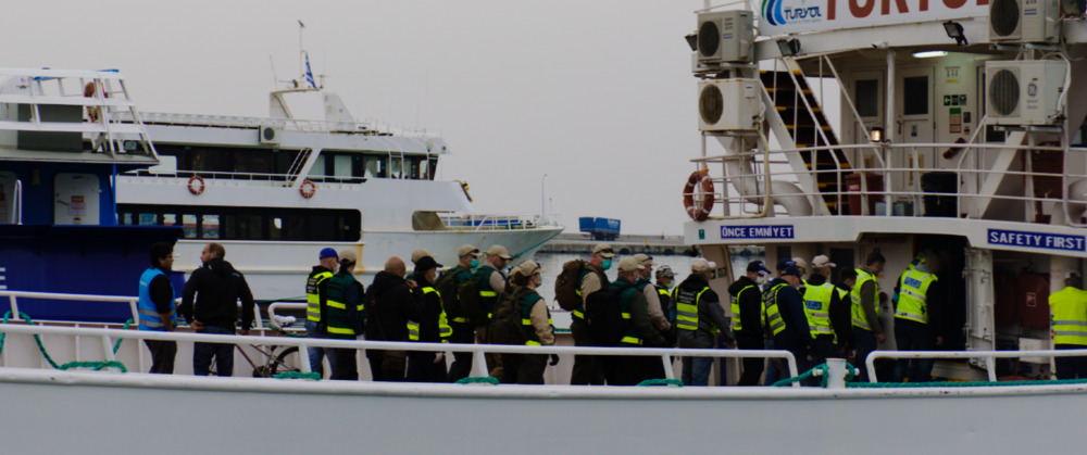 Officials Escort Refugees onto Boat for Deportation to Turkey