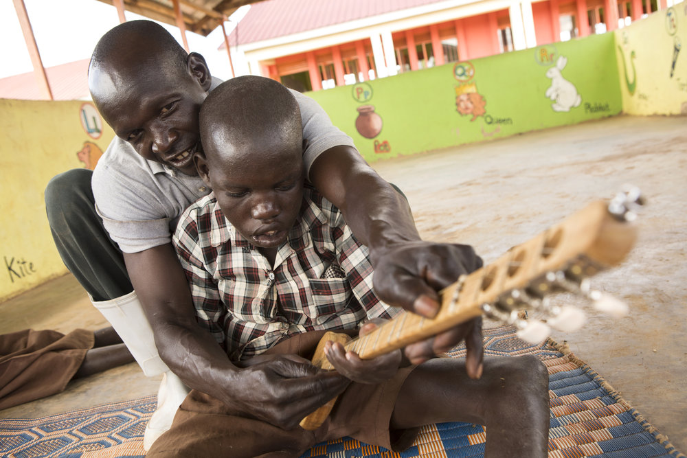 "Simon Peter Ojok helps 23-year-old Nill Kidega strum a small guitar during a break from classes on May 22, 2017. Workers at Hope for Humans credit love as much as medication in treating nodding syndrome. Many children call their caretakers ""daddy"" or ""mommy"" because their condition left them unconscious for years and they have no memory of their parents."