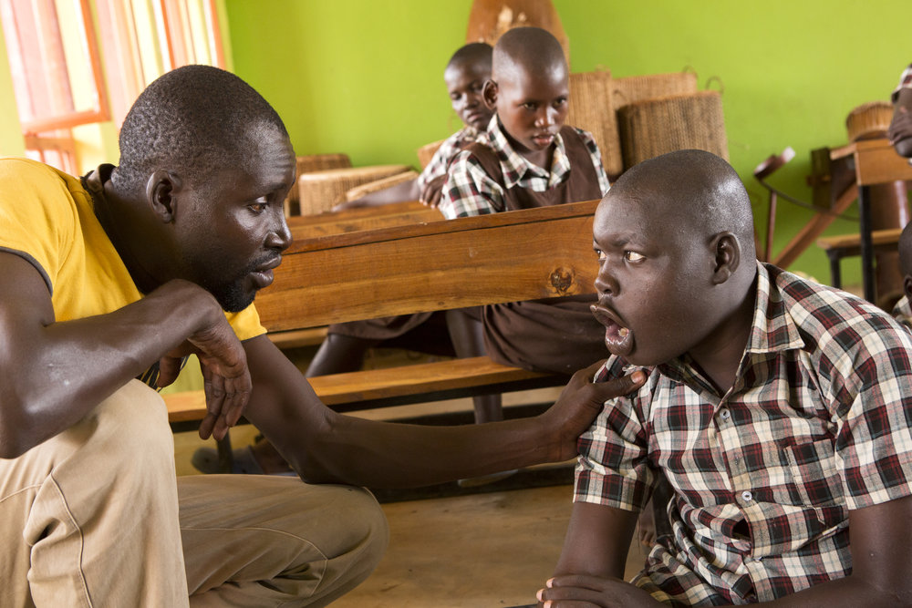 Okello Kenneth (left) tries to talk with Okwera Alfred during class on May 23, 2017.