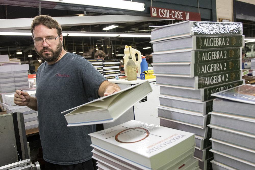 - Clay Lankford of Utica stacks rebound books at Houchen Bindery in Utica, Nebraska, on July 6, 2017.
