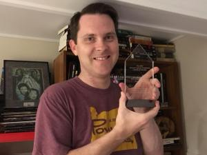 Horror writer and artist Greg Chapman with his award from the Horror Writers Association.