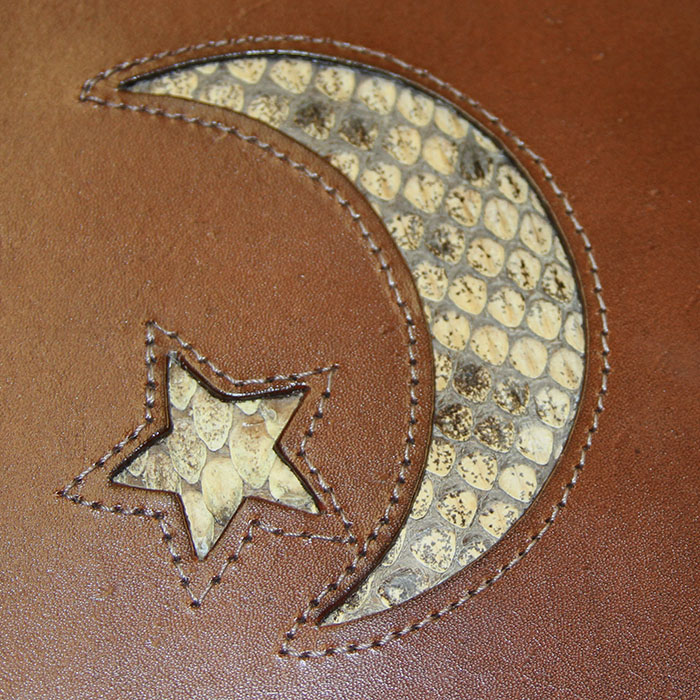 DIE CUT INTO LEATHER WITH PERIMETER STITCHING