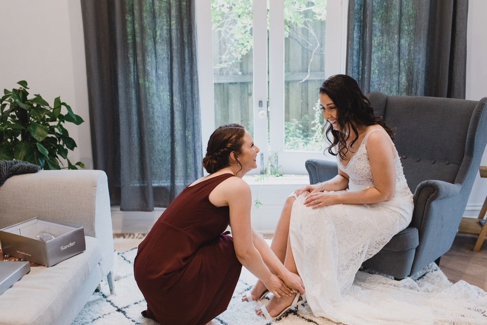Me helping Lisa put on her bridal shoes, December 2018.