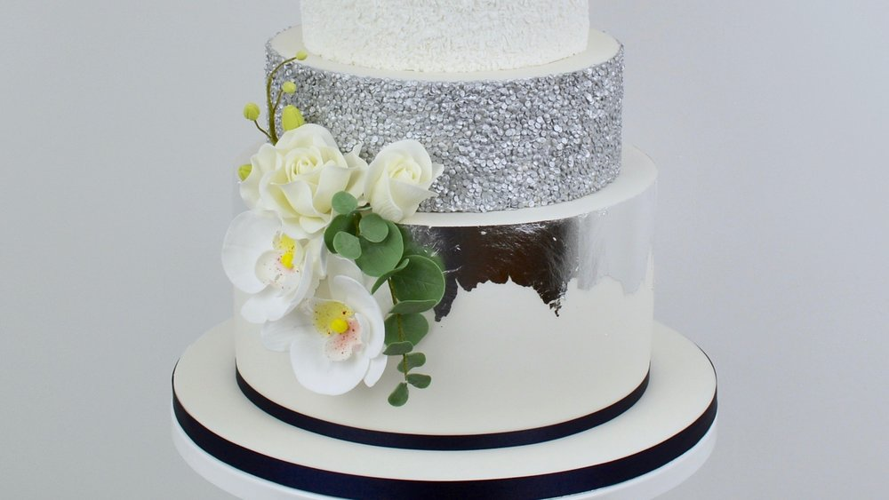 Silver Orchids - Delicate white orchids and ivory tea roses with striking edible silver detailing and a touch of midnight blue for a beautifully elegant wedding cake