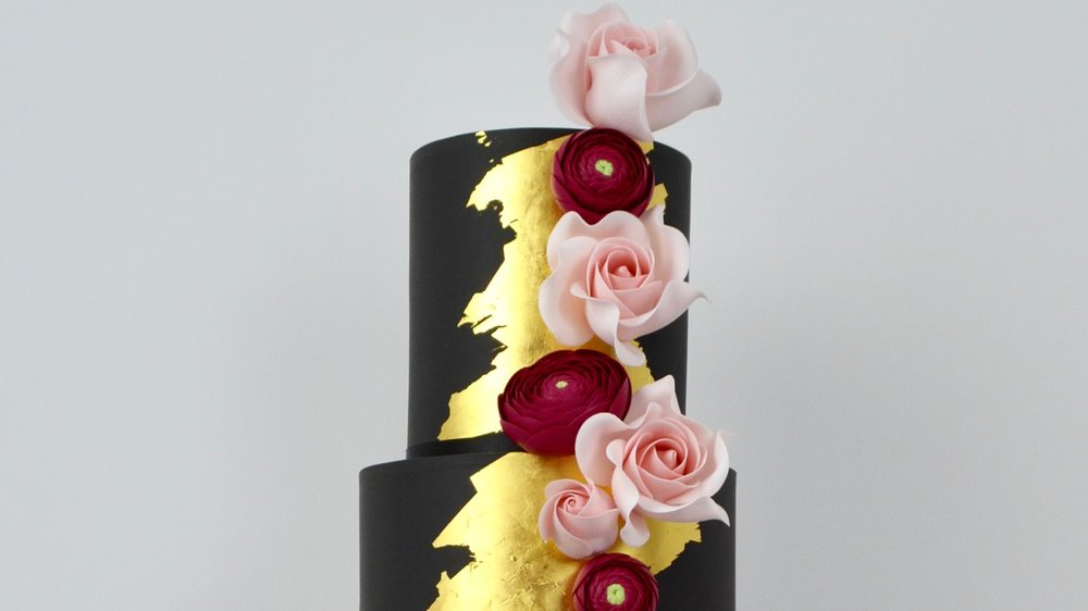 Black and Gold - Contrasting black and gold finishes combined with ruby red ranunculus and blush pink roses for a romantic yet dramatic wedding cake