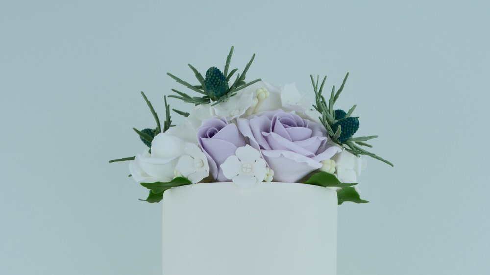 Sea Holly and Roses - Beautiful sea holly and delicate roses add a stunning crown to a strikingly elegant champagne lustre and broken gold leaf wedding cake