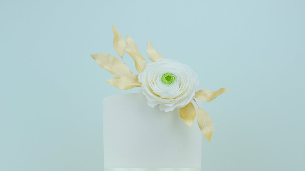 Ranunculus and Gold Sequins - Delicate white ranunculus with gold pearl foliage, sequin icing and contrasting plain tiers to create a stunning wedding cake