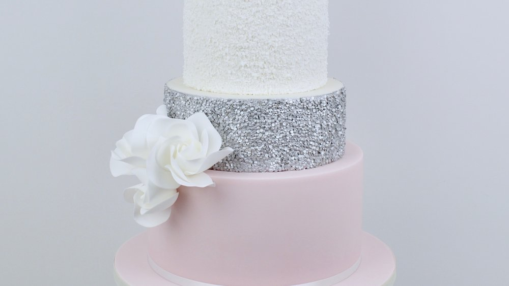 Blush and Silver Sequins - Beautiful contemporary white roses combined with silver sequin icing and pale pink and textured white tiers to create a striking wedding cake