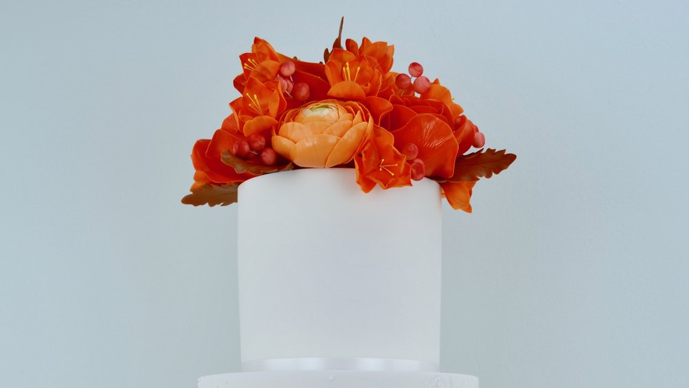 Autumn Lace - A stunning splash of burnt orange and Autumn shades in roses, ranunculus, fresias and oak leaves for a spectacular seasonal wedding cake