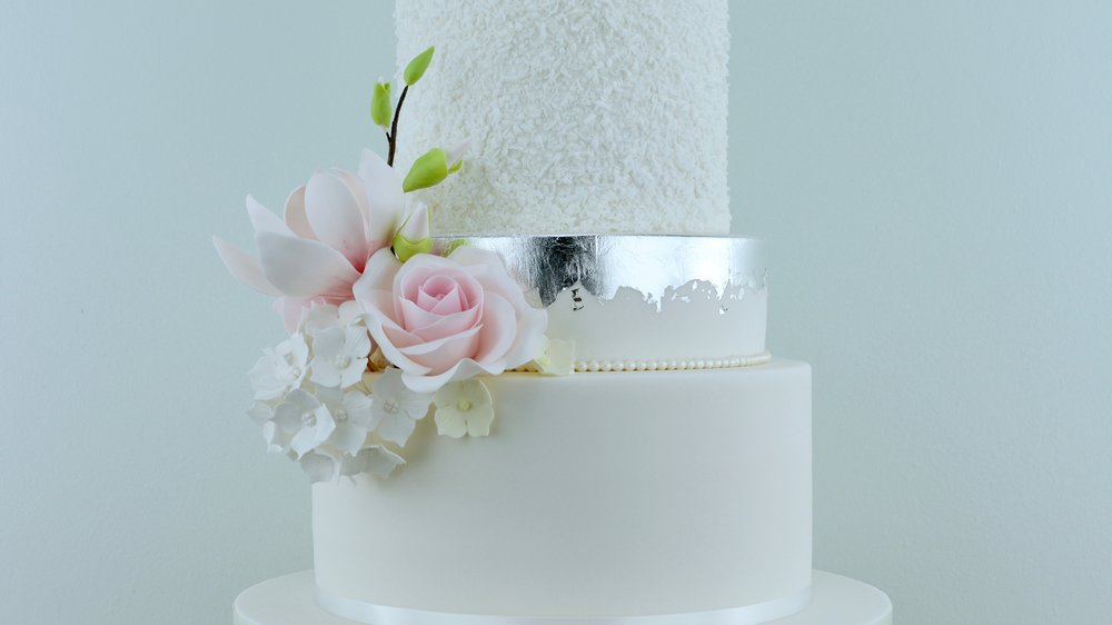 Magnolia Roses and Peony - A sublimely elegant wedding cake with silver leaf, a fluffy textured tier, pale pink roses, magnolias and a striking peony