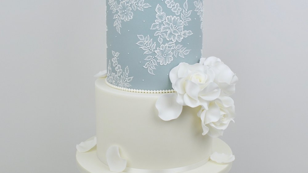 White Roses and Lace - Elegant white roses, cascading sugar rose petals and embroidery lace icing combine to create a truly beautiful wedding cake