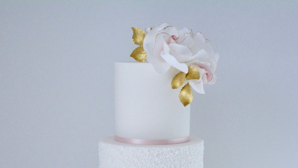 Blush and Gold Roses - Fluffy textured icing and delicate sugar roses with a hint of blush colouring and gold foliage for a beautifully elegant celebration cake