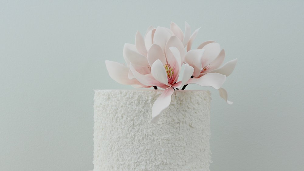 Magnolias - Textured tier with vibrant pink magnolia flowers crowning this beautiful celebration cake