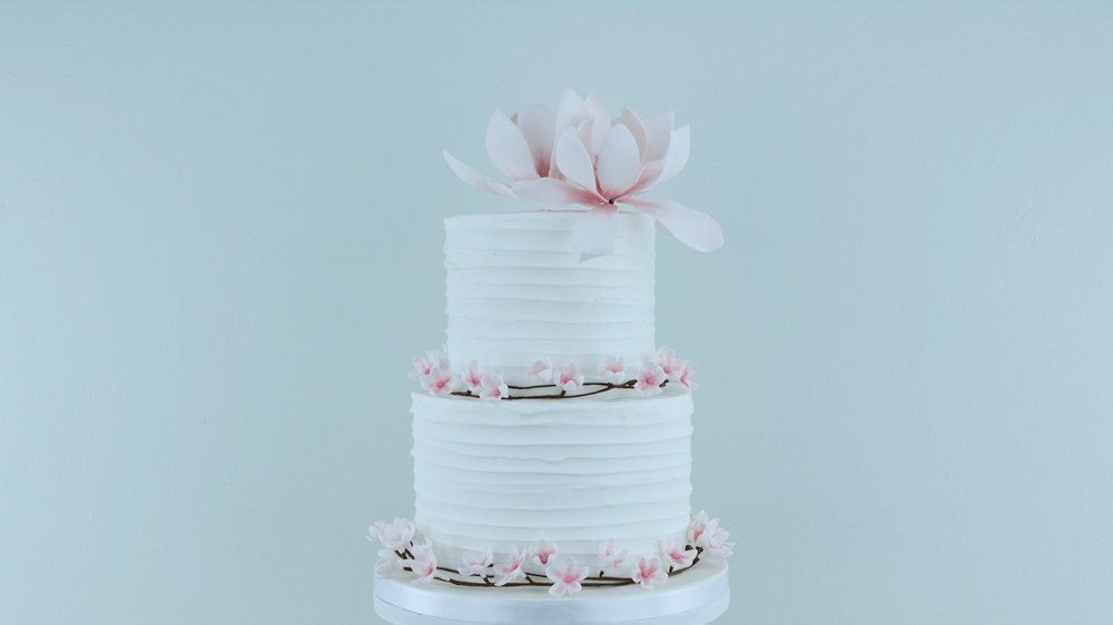 Magnolia and Blossom - Gorgeous pink cherry blossom and striking magnolia flowers with rustic icing for a beautiful celebration cake