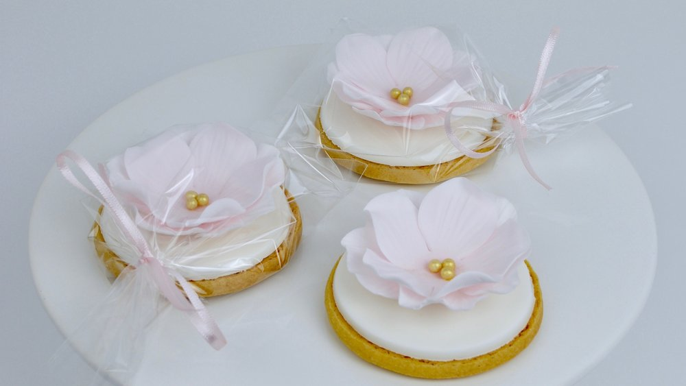 Iced Cookies - With delicate sugar flowers our iced cookies make beautiful and eye-catching wedding favours. Choose a bespoke design to mark your special day with your wedding guests.