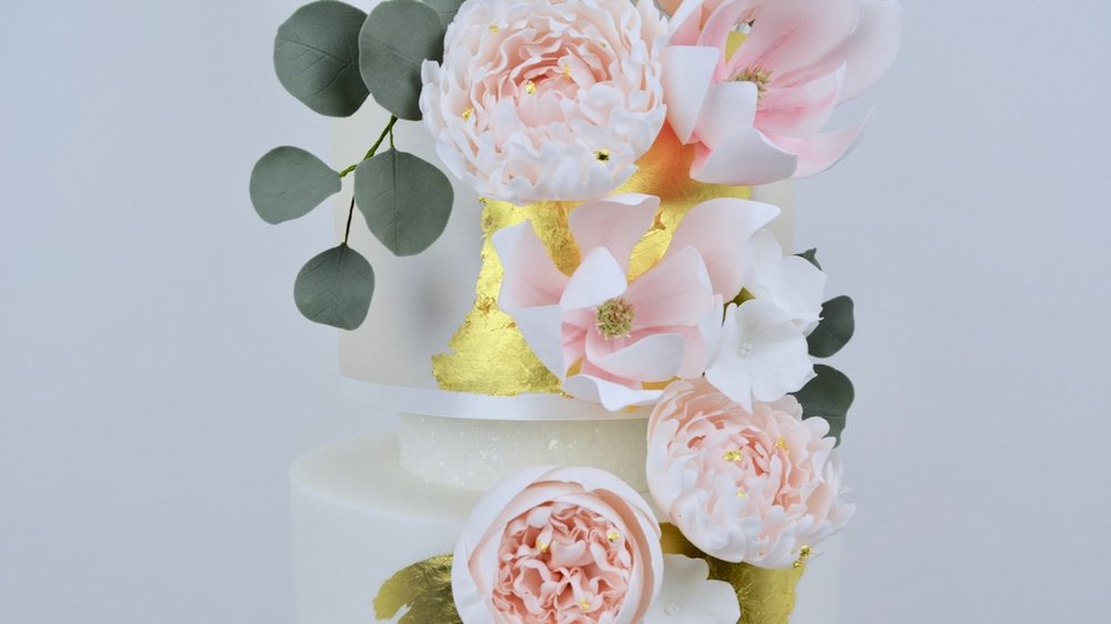 Peony & Magnolia - A beautifully slender and elegant wedding cake with gorgeous peonies, magnolia, hydrangea and foliage against striking whites, champagne and gold
