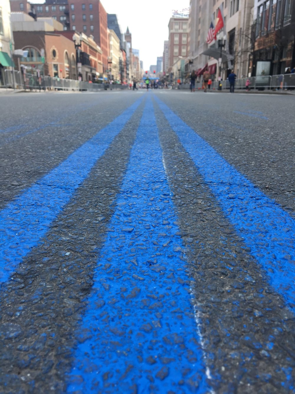 """Within the law enforcement community, thin blue lines are a symbol of the role police officers play in a community be separating good and evil in society. Runners will have a blue-line guided path to the finish time as they make their final left turn at Hereford Street."" - BPD"