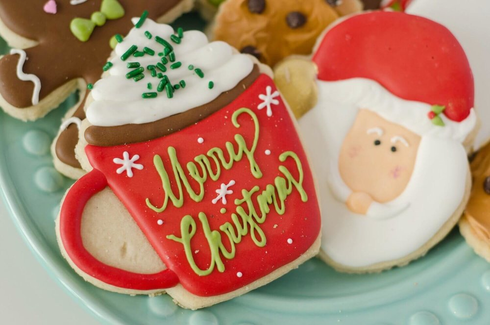 The cutest decorated cookies for a Christmas holiday party with hot cocoa mugs and Santa Claus. See more from this Cookies for Santa party on www.minteventdesign.com - styled by Austin, Texas based party planner Mint Event Design. #holidayparty #holidaypartyideas #christmaspartyideas #christmascookies #holidaydesserts