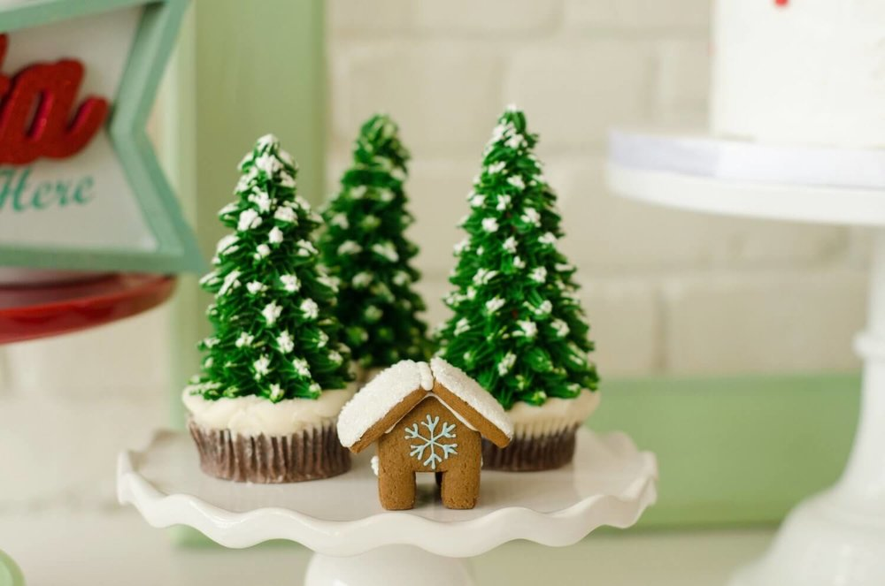 The most festive way to frost cupcakes for holiday parties - Christmas Tree cupcakes with a mini gingerbread house. See more from this Cookies for Santa party on www.minteventdesign.com - styled by Austin, Texas based party planner Mint Event Design. #holidayparty #holidaypartyideas #christmaspartyideas #gingerbreadhouse #christmascupcakes #holidaydesserts