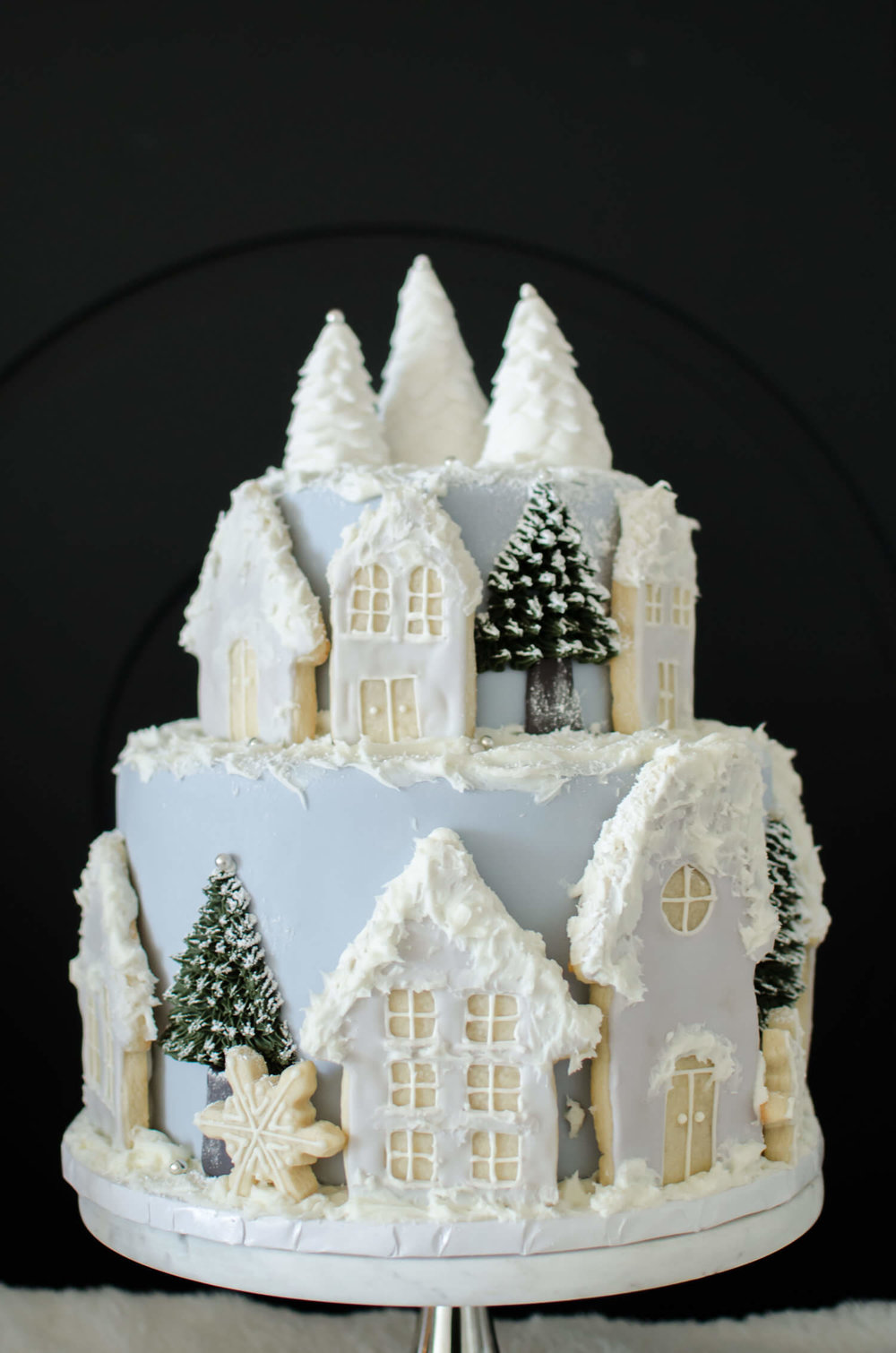 winter bridal shower cake idea with a snowy village scene created with frosted cookies and trees
