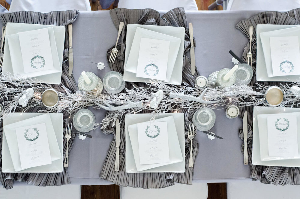 Loving this white and gray winter party tablescape. Pretty rouched linens and hand-calligraphed menus. See more ideas from this Winter Wonderland themed Bridal Shower Inspiration created by Mint Event Design www.minteventdesign.com #winterweddingideas #weddingwedding #bridalshowerideas #winterwonderland #tablesettings #tablescapes