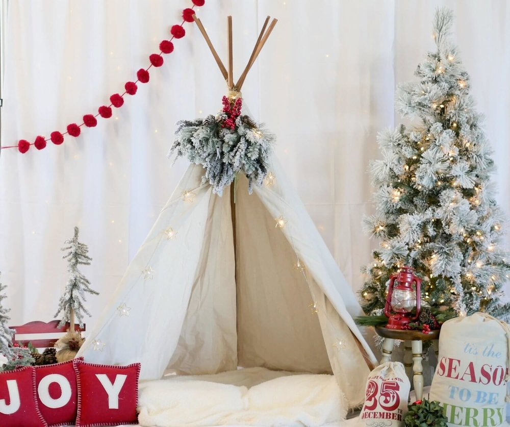 Create the ultimate holiday photo booth backdrop by hanging string lights behind the white fabric backdrop to diffuse the lighting. Hanging a pom pom garland in the front will add a pop of color. Click for more Christmas Photo Booth Tips from Mint Event Design www.minteventdesign.com #holidayphotography #photoboothideas #christmaspartyideas #photobooth #holidayparties