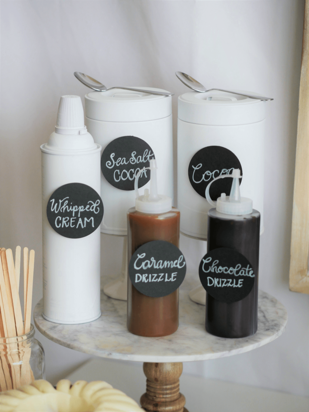 Yummy Whipped cream, caramel and chocolate drizzle are the Hot Chocolate Toppings of choice for this super stylish and easy DIY Hot Cocoa and Coffee Station. Styled by party stylist Mint Event Design. #partyideas #partyinspiration #hotchocolate #hotcocoa #coffeebar #coffeestation #winterparty #winterwedding