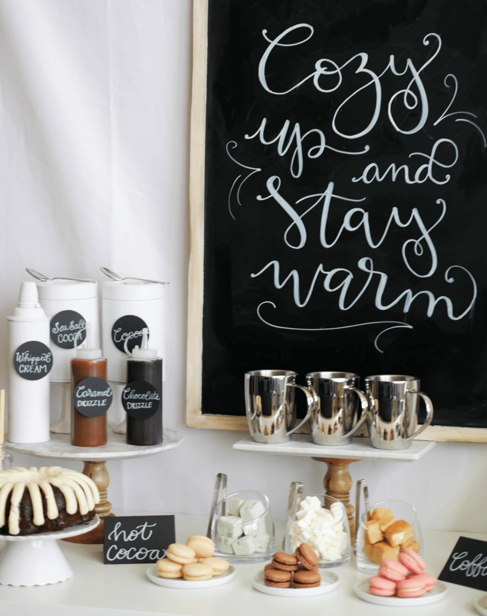 Cozy up and stay warm with this beautiful DIY Chalkboard Sign. It's the perfect backdrop for this Hot Cocoa and Coffee Station. Styled by party stylist Mint Event Design. #partyideas #partyinspiration #hotchocolate #hotcocoa #coffeebar #coffeestation #winterparty #winterwedding #chalkboardsign