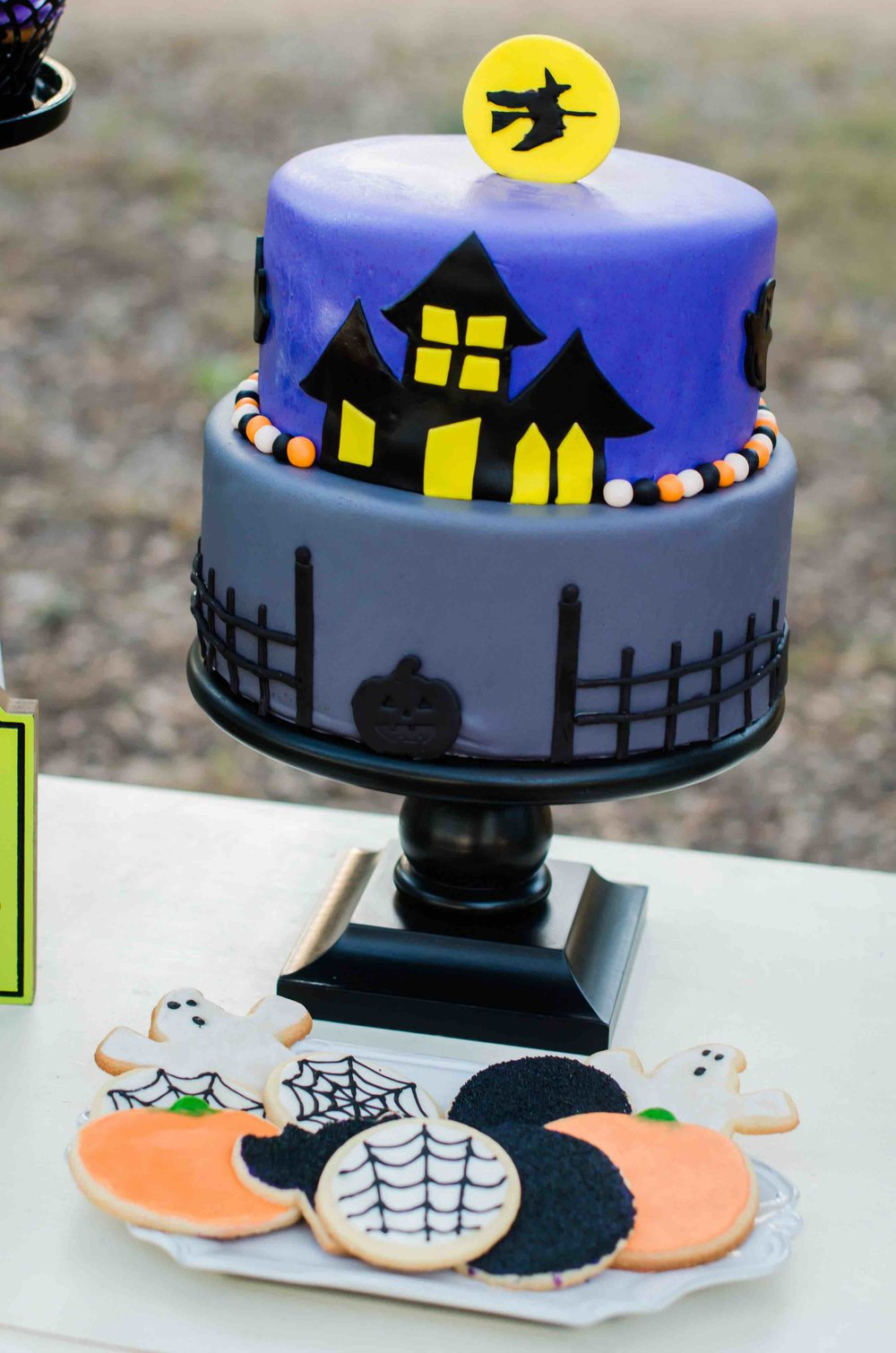 A Halloween Cake decorated with a haunted house, a witch flying on her broomstick and even a black pumpkin. Click to see all the Halloween Party Ideas that you can re-create for your very own Halloween Kids Party. Styled by party stylist Mint Event Design. #halloween #partyideas #partyinspiration #halloweencake #desserttable #halloweencookies