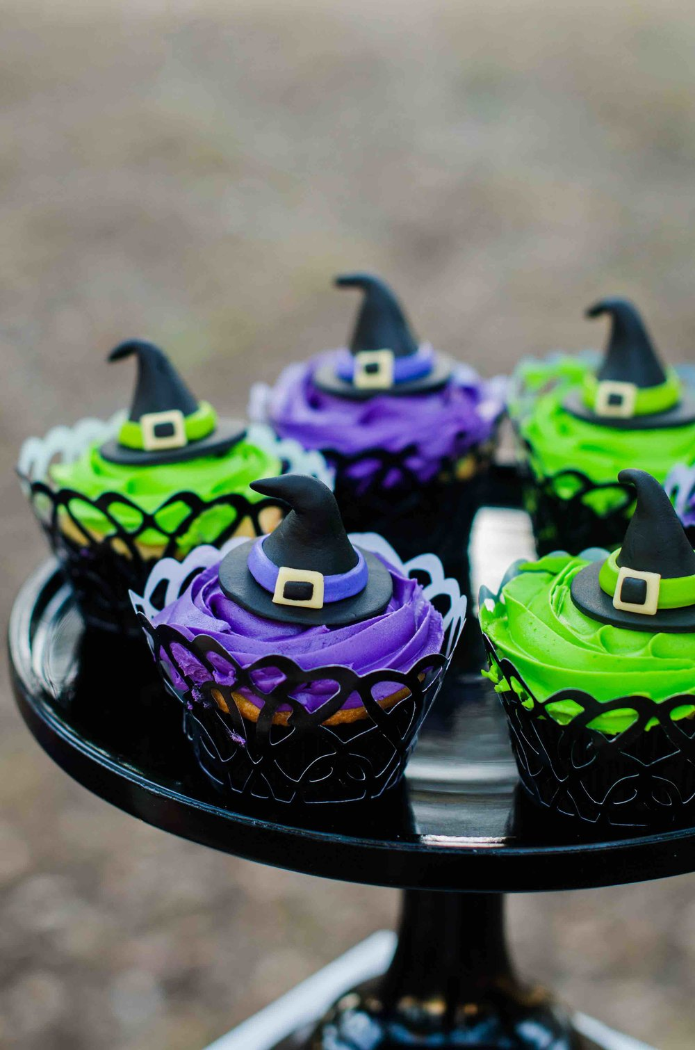 The perfect Halloween Party Cupcakes topped with a witches hat and displayed in decorative cupcake wrappers. Click to see all the Halloween Party Ideas that you can re-create for your very own Halloween Kids Party. Styled by party stylist Mint Event Design. #halloween #partyideas #partyinspiration #partydecor #desserttable #halloweencakes #halloweencupcakes