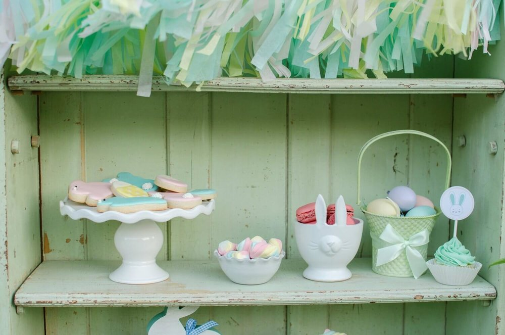 Easter party treats are displayed on a shelf for guests to choose their favorite.. See more Easter Garden Party Ideas for Kids on Mint Event Design www.minteventdesign.com #easterparty #gardenparty #desserttable