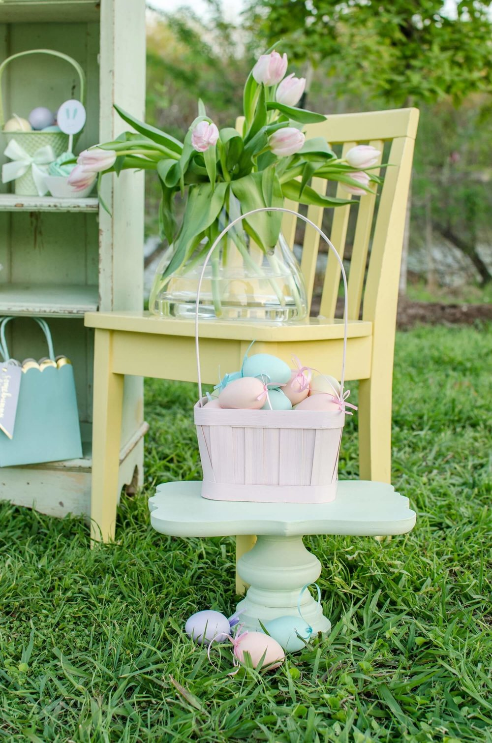 Dress up your Easter Garden Party dessert table with a pretty wooden chair that holds a fresh bouquet of tulips and a cute basket of eggs on a cake stand. See more Easter Garden Party Ideas for Kids on Mint Event Design www.minteventdesign.com #easterparty #gardenparty #partyideas