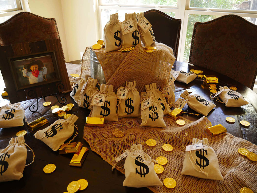 Cowboy themed party goodie bags - bank bags willed with toys, bubbles, candies and crayons and of course chocolate gold coins from the Wild West Bank / Styled by Carolina from MINT Event Design / www.minteventdesign.com #wildwest #cowboy #birthdayparty #partyideas #partyfavors