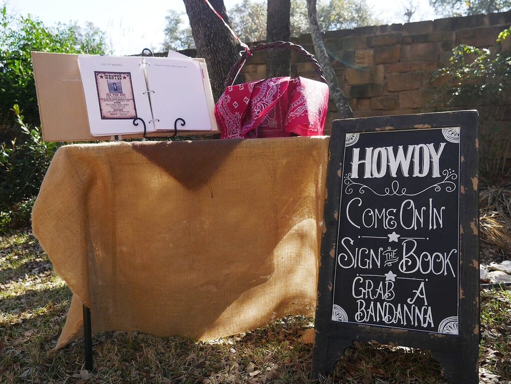 Howdy - it's a birthday guest book sign with bandanas for the guests. Click to find many more easy Cowby Birthday Party Ideas / Styled by Carolina from MINT Event Design / www.minteventdesign.com #wildwest #cowboy #birthdayparty #partyideas #boybirthday