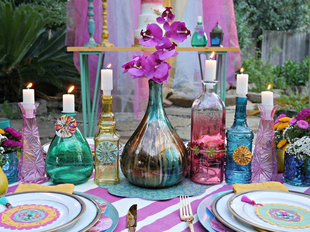 Jewel toned glasses with candles are perfect table decor at a gypsy inspired party. Styled by Mint Event Design www.minteventdesign.com #tablesetting #tablescapes #bohochic