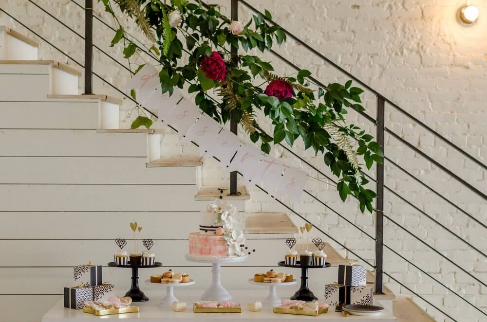 Beautiful and chic Dessert Table idea with floral garland