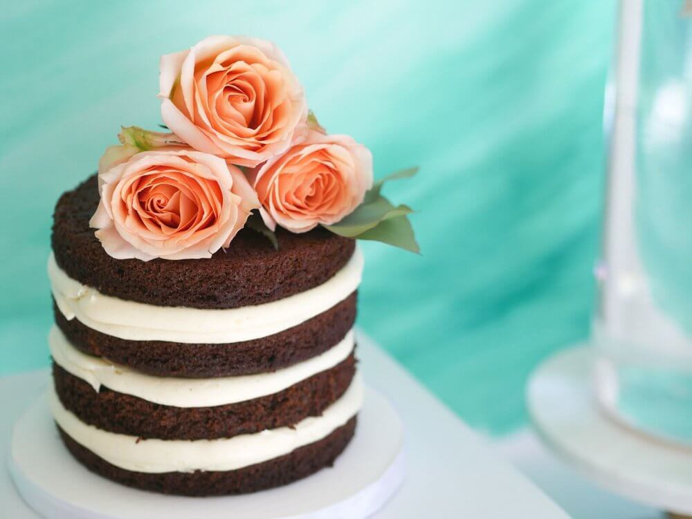 Naked cake with coral fresh flowers