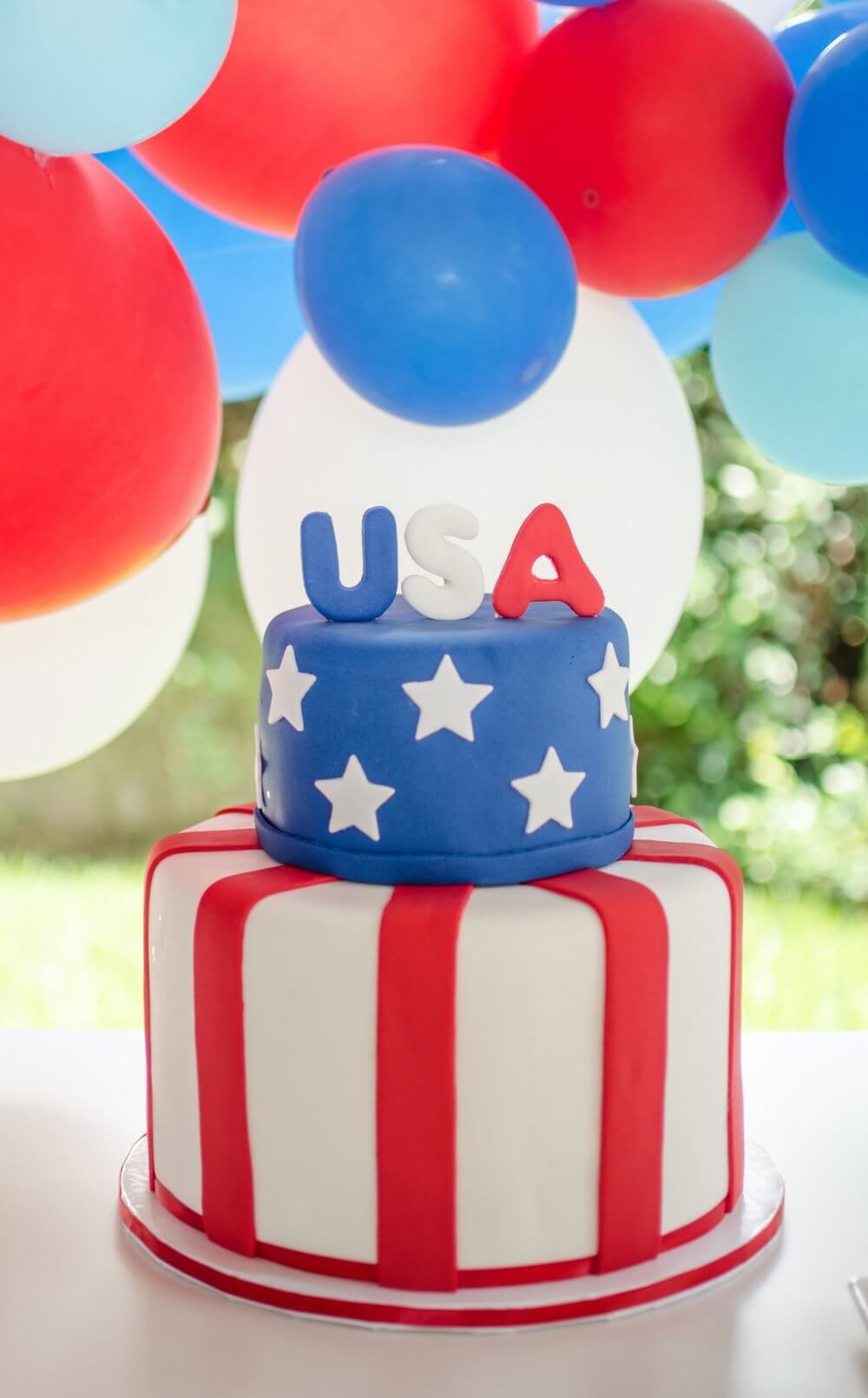 Beautiful handmade red, white, and blue patriotic fondant cake created by Sweet Carousel Cakes.