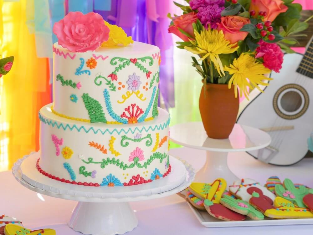 Two-tier fiesta party cake with ornate piping design in bright colors. Sombrero, cactus, chili pepper cookies too.