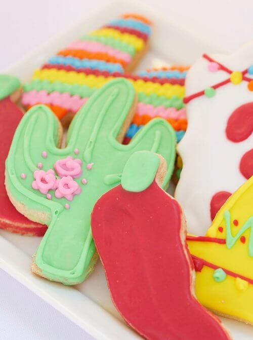 Cactus and chili pepper sugar cookies are almost too cute to eat. Perfect choice for a fiesta themed birthday party. See more on www.minteventdesign.com #kidsbirthdayparty #fiestaparty #disneycoco #partyideas #girlbirthdayparty #cocobirthdayparty #sugarcookies