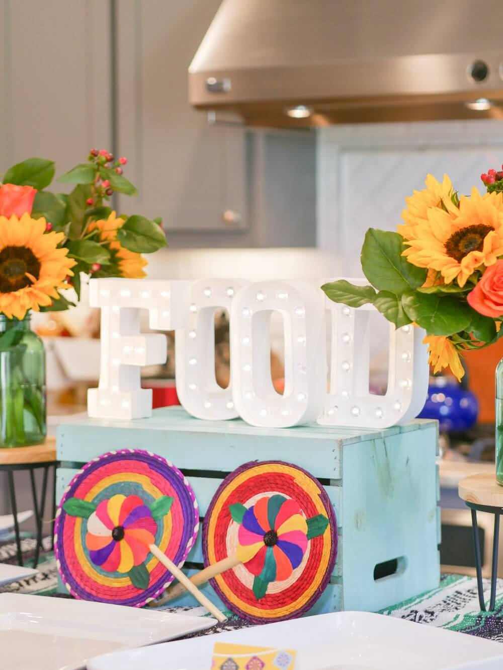 Fiesta food table with FOOD marquee sign and Mexican decor.