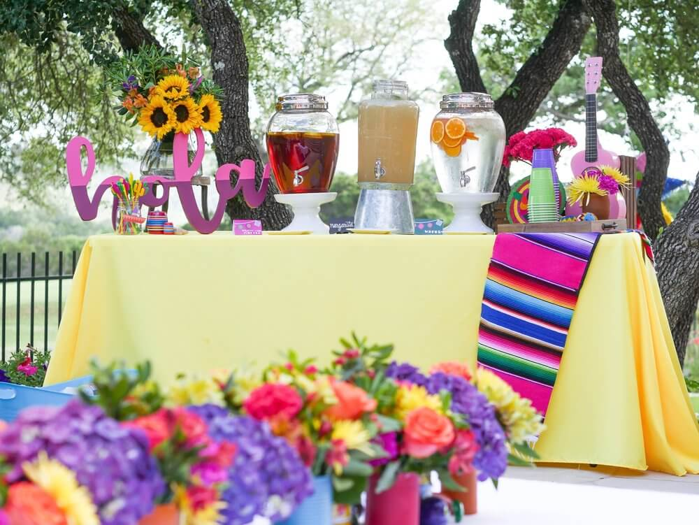 """Beverage table was decorated with fiesta flare! An """"Hola"""" sign, Mexican blanket, mini pink guitar, and lots of colorful decor set the stage for a great drink!"""